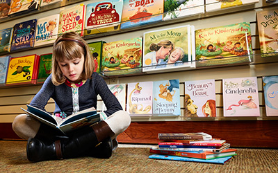 Young girl sitting down and reading in the book section of the Children's Shop at Hartville Kitchen