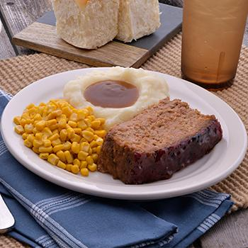 A plate with a meatloaf, corn, and mashed potatoes with gravy