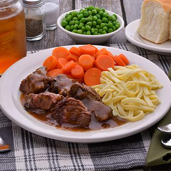 A dinner plate on a table next to a small bowl of green peas and a plate of rolls