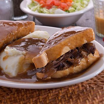 A plate with mashed potatoes and a hot sandwich covered with gravy