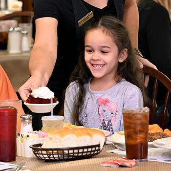 A girl smiling and being served a nice dessert at Hartville Kitchen