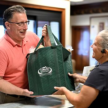 A man picking up a green bag full of his catering order from Hartville Kitchen