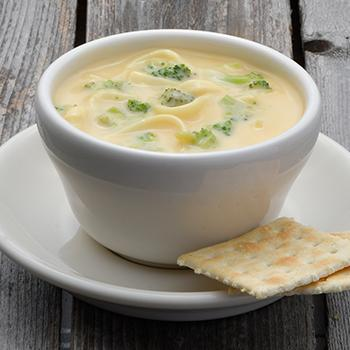 A bowl of soup on a plate with crackers