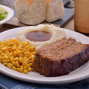 A dinner plate with meatloaf, mashed potatoes and gravy, and corn