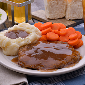 A dinner plate with swiss steak, mashed potatoes and gravy, and sliced carrots