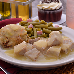 A plate with turkey, stuffing, and green beans