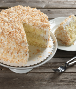 coconut cream cake on a cake stand with a piece missing
