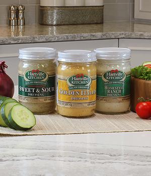 three different jars of Hartville Kitchen refrigerated salad dressing