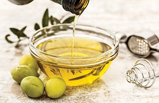 Extra virgin olive oil being poured into a glass bowl