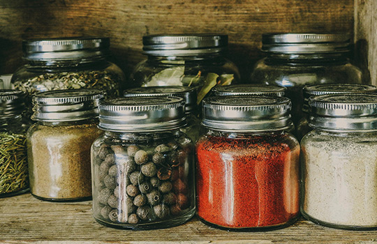 A variety of jars filled with flavored oil ingredients