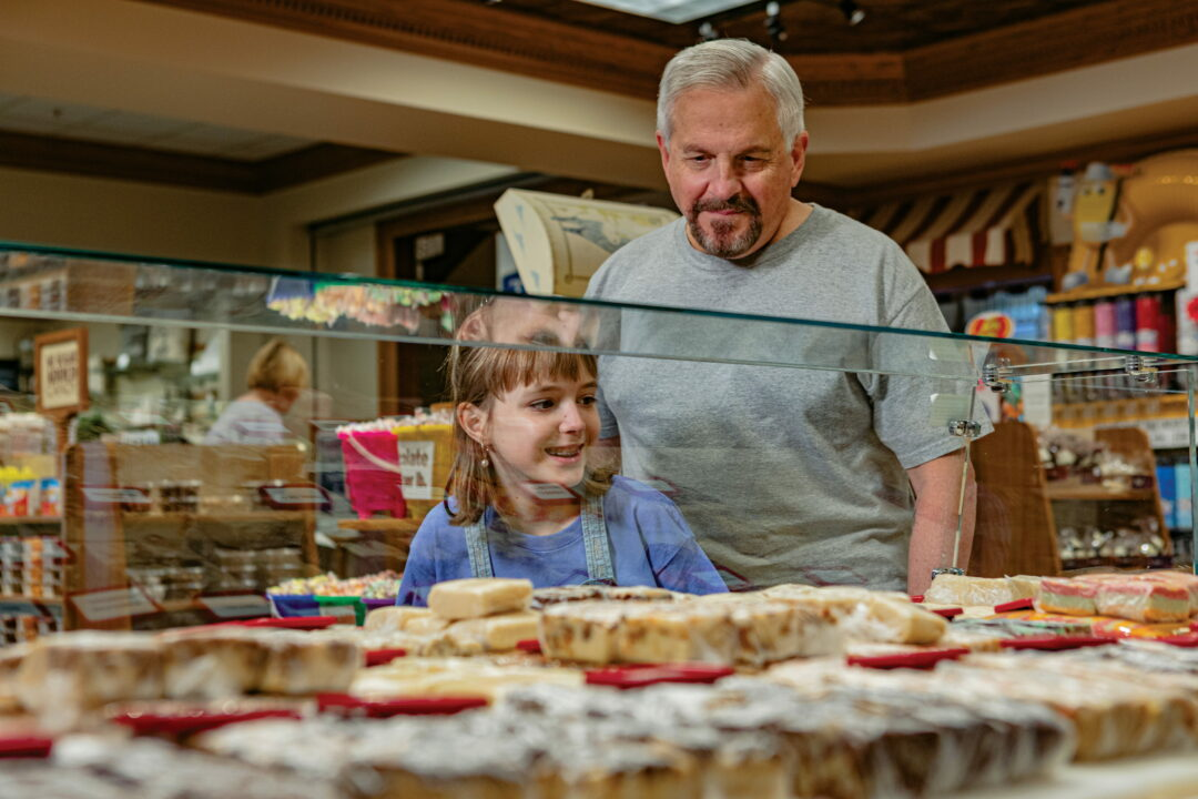 An older gentleman and his grandaughter looking at confections through a glass display case