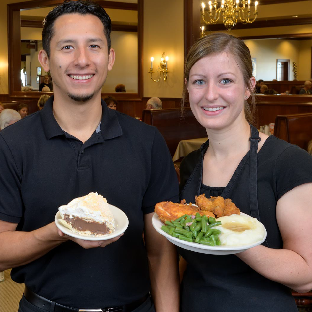 A man and a lady holding plates of food and smiling at the camera