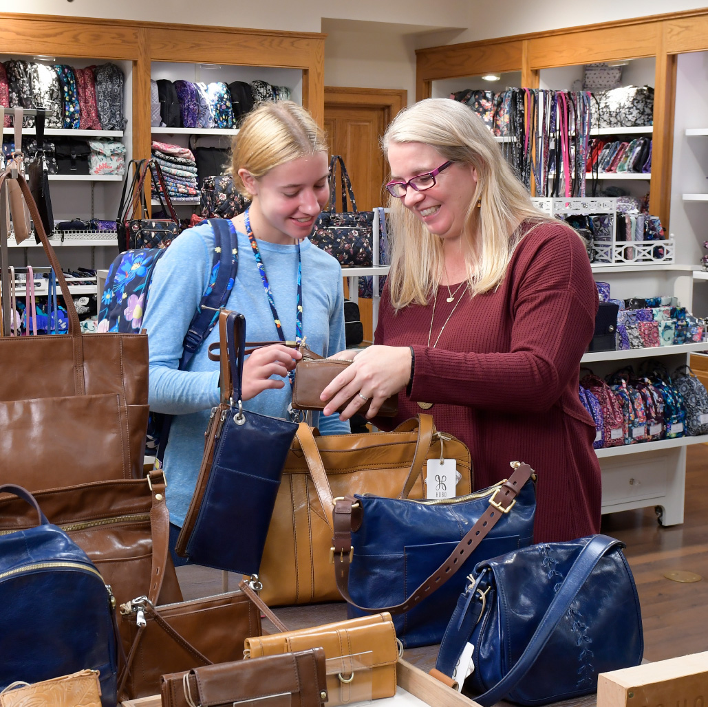A woman and her daughter looking at different purses in The Shops at Hartville Kitchen