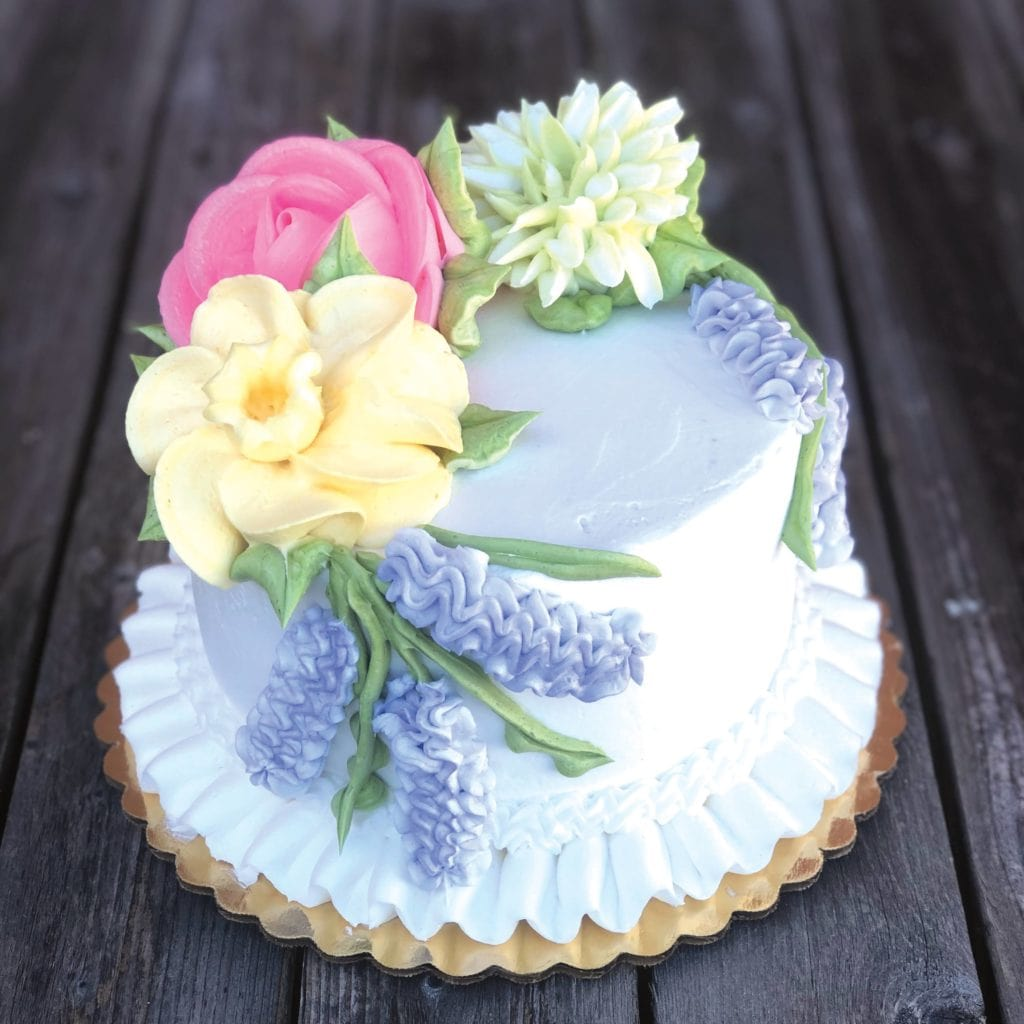 Frosted cake with colorful flowers from Hartville Kitchen Bakery